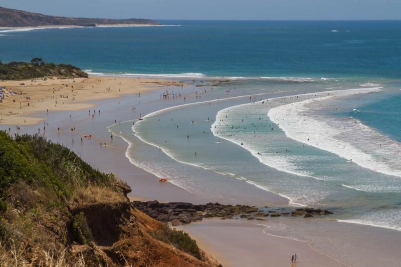 Playa con surferos
